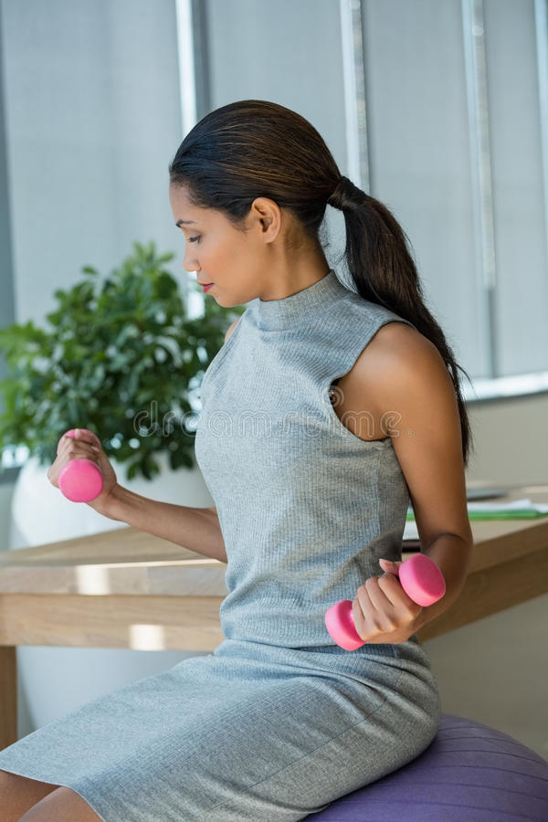 Beautiful executive lifting dumbbells while exercising on fitness ball. In office royalty free stock photography