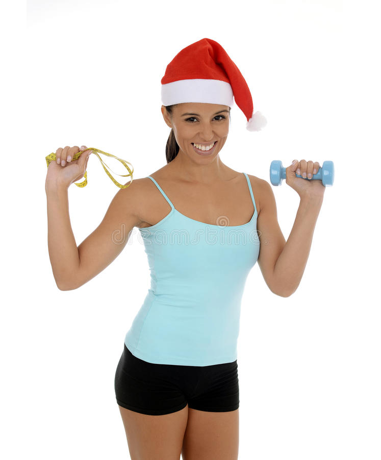 Beautiful and exotic hispanic woman in Christmas Santa hat holding weight and measure tape stock photo