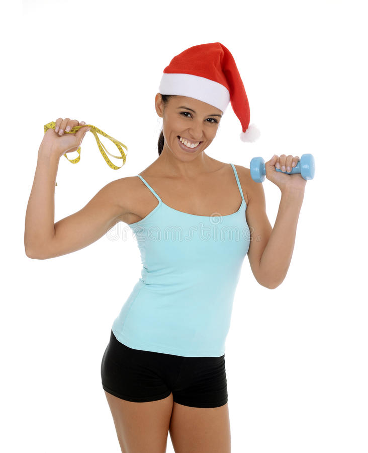 Beautiful and exotic hispanic woman in Christmas Santa hat holding weight and measure tape royalty free stock photography
