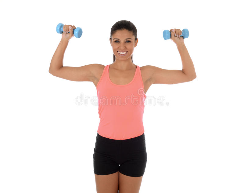 Beautiful and exotic hispanic woman holding hand weights training in fitness concept royalty free stock images
