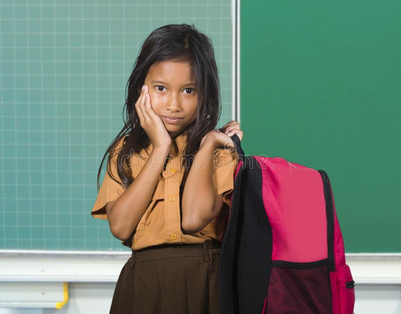 Beautiful and exotic looking female child in school uniform carrying student bag smiling in front of classroom blackboard in back. Portrait of beautiful and stock photo