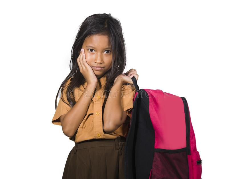 Beautiful and exotic looking female child in school uniform carrying student bag smiling isolated on white background in back to. Portrait of beautiful and royalty free stock photos