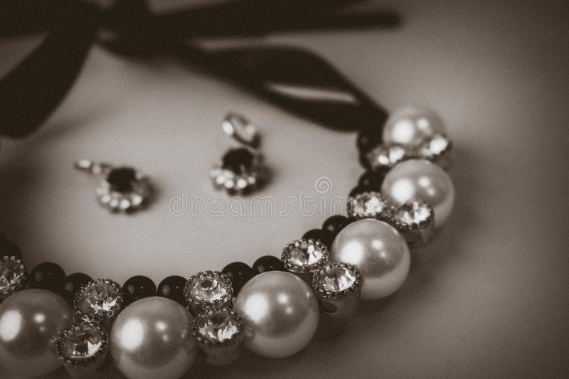 Beautiful expensive precious shiny jewelry fashionable glamorous jewelry, necklace and earrings with pearls and diamonds. Diamonds on a black and white stock photo