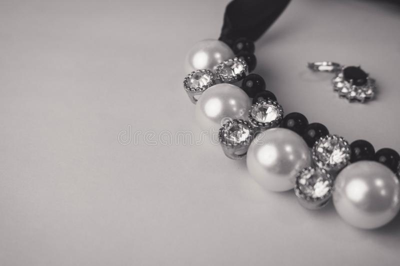 Beautiful expensive precious shiny jewelry fashionable glamorous jewelry, necklace and earrings with pearls and diamonds. Diamonds on a black and white stock photography