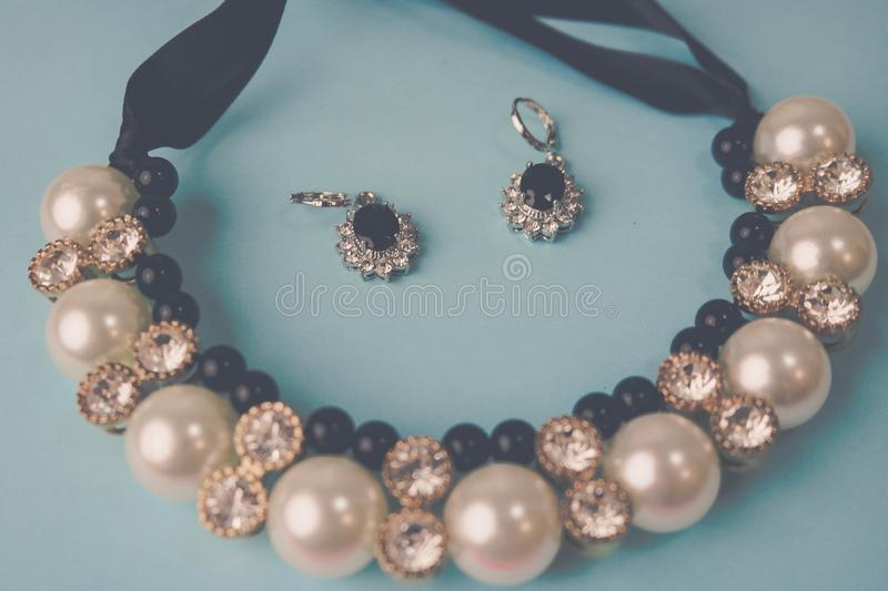 Beautiful expensive precious shiny jewelry fashionable glamorous jewelry, necklace and earrings with pearls and diamonds. Diamonds on a blue background. Flat stock image