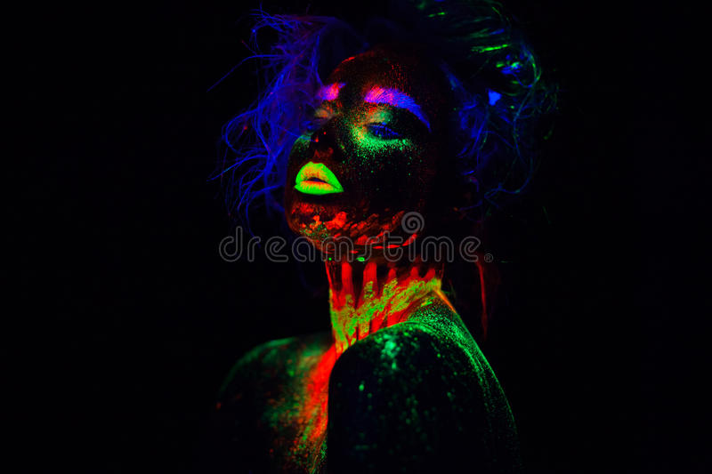 Beautiful extraterrestrial model woman with blue heair and green lips in neon light. It is portrait of beautiful model stock photos
