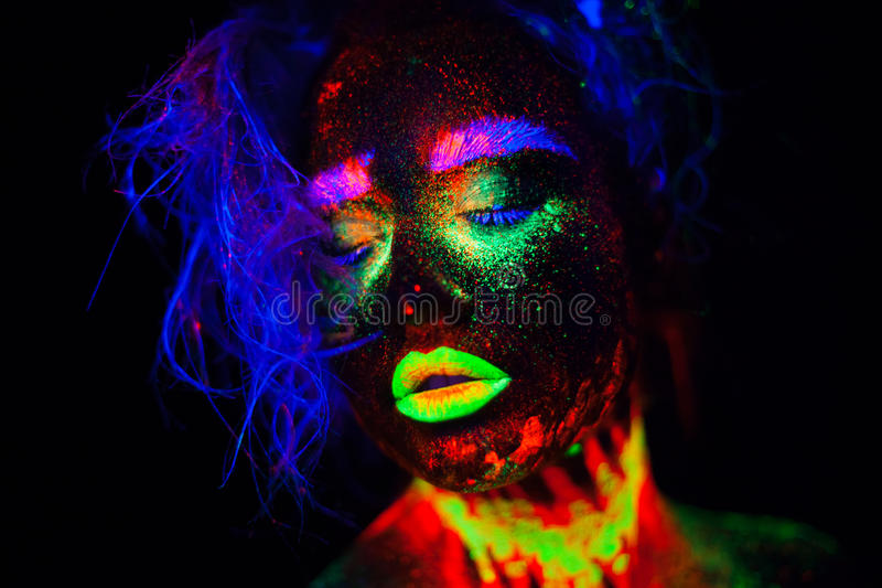 Beautiful extraterrestrial model woman with blue heair and green lips in neon light. It is portrait of beautiful model royalty free stock images