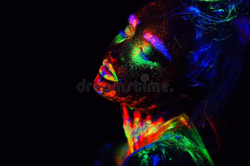 Beautiful extraterrestrial model woman in neon light. It is portrait of beautiful model with fluorescent make-up, Art. Close up beautiful extraterrestrial model royalty free stock photos