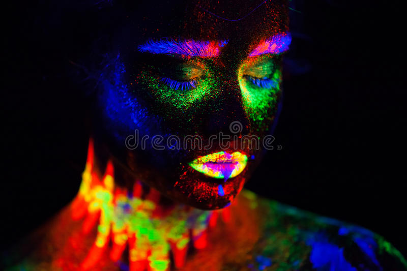 Beautiful extraterrestrial model woman in neon light. It is portrait of beautiful model with fluorescent make-up, Art stock photography
