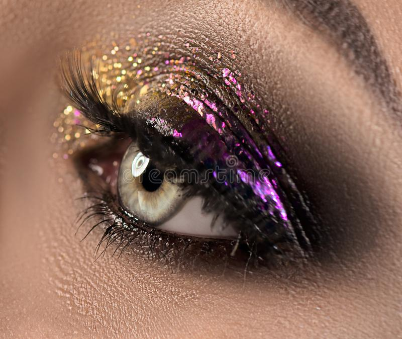 Beautiful eye makeup with colorful sparks. Beauty bright fashion holiday smoky eyes makeup royalty free stock photo