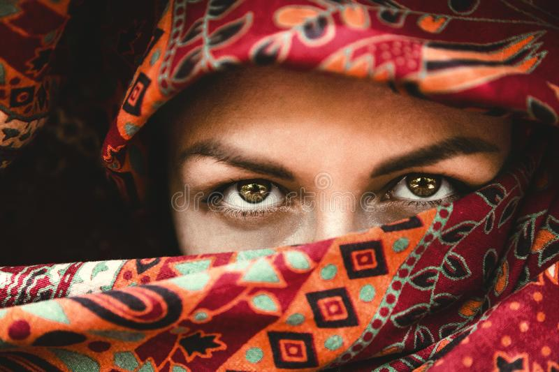 Beautiful eyes. The face of a woman in an red Indian scarf. Expressive look. Oriental beauty royalty free stock photos