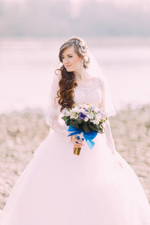 Beautiful fabulous curly bride with stylish bouquet standing on the beach. royalty free stock photos