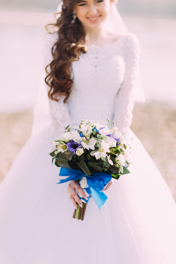 Beautiful fabulous curly bride with stylish bouquet standing on the beach. stock images