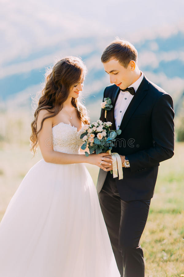 Beautiful fabulous happy bride with bouquet and stylish groomholding hands on the background of rocks in mountains royalty free stock photo