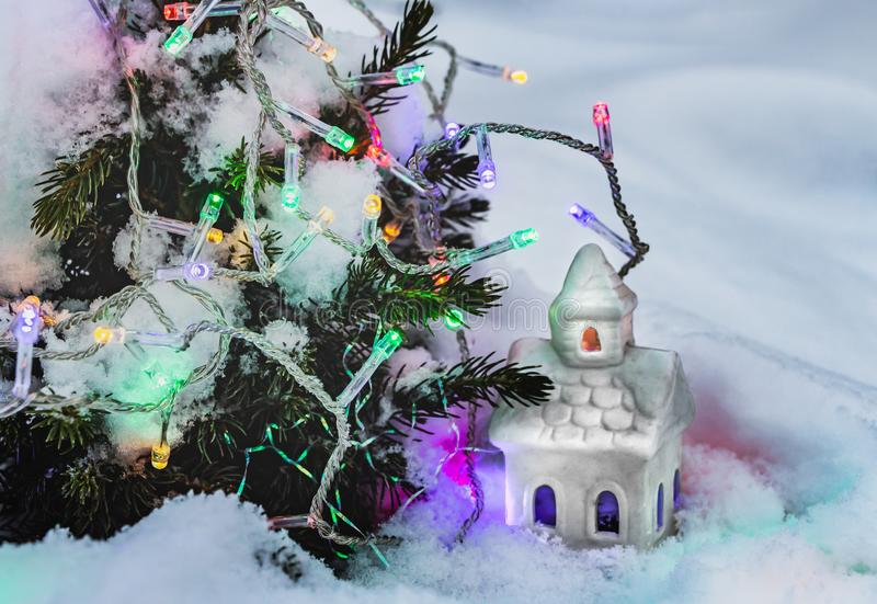 A beautiful fabulous little white house with yellow and blue lights in the windows and garlands of burning colorful lamps on a. Little Christmas tree wiht snow royalty free stock photo