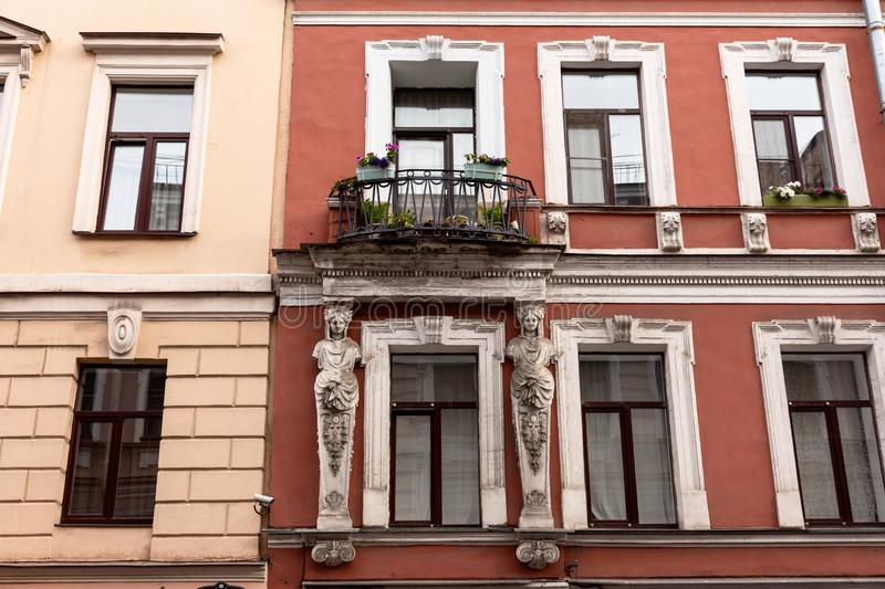 Facade of an old building. Beautiful facade of an old building with an elegant balcony with flowers and two caryatids stock image
