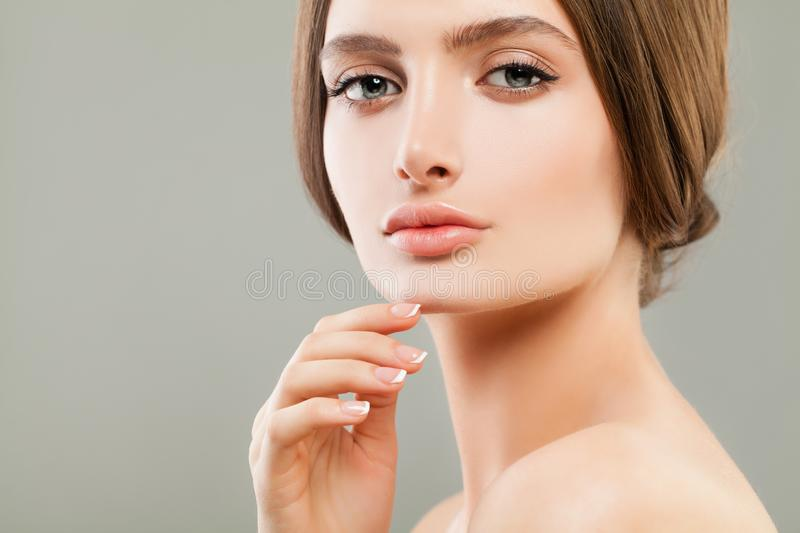 Beautiful face closeup. Pretty woman with perfect skin and french nails manicure stock image