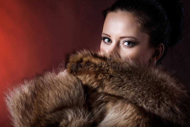 Portrait of beauty woman in luxury winter fur coat. Beautiful face and impressive eyes brunette woman looking at camera. Dressed in luxury winter fur coat. Shot royalty free stock photos
