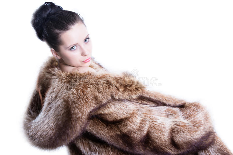 Pretty woman in luxury winter fur coat. Beautiful face and impressive eyes brunette woman looking straight up to the camera. Dressed in luxury winter fur coat stock image