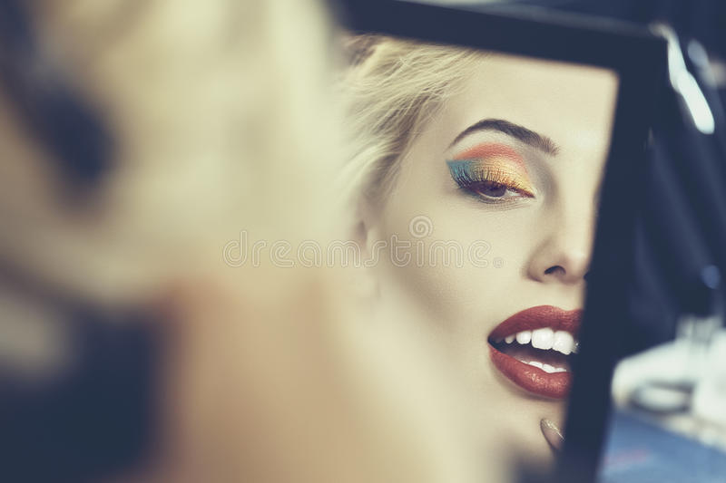 Beautiful face in the mirror. Detail of beautiful sensual woman face in a mirror. Beauty makeup and cosmetics treatment. Shallow depth of field and mate color stock photo