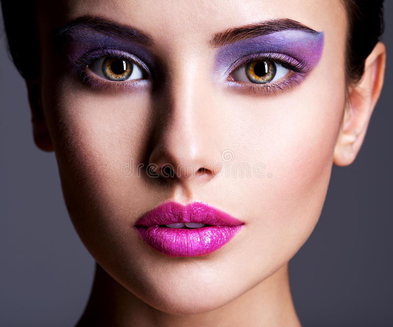 Beautiful face with purple eye make-up. fashion makeup royalty free stock photos