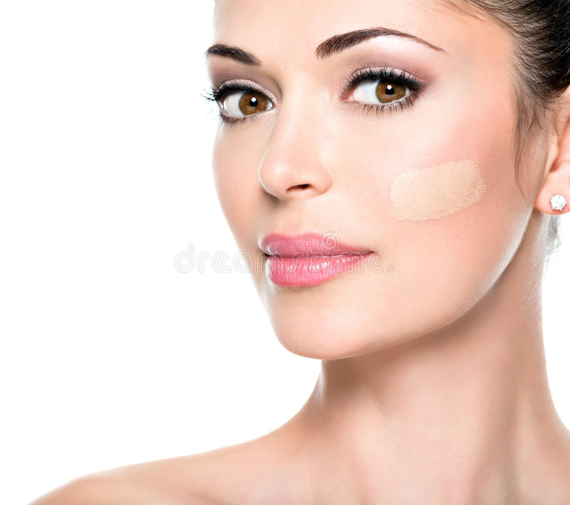 Beautiful face of woman with cosmetic foundation on a skin. stock photo