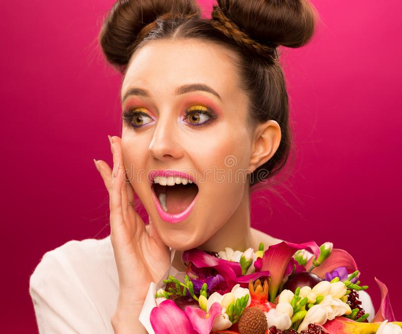 Face, fun, fruit bouquet, pink. Beautiful face woman, has fun eyes, smile lips, decorative pink make up, holds luxury fruit flowers bouquet: pink callas, garnet royalty free stock photo