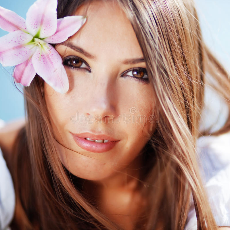 Beautiful face of woman with lily in her hair stock image