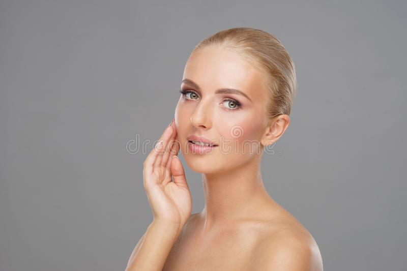 Beautiful face of young and healthy girl. Skin care, cosmetics and face lifting concept. Beautiful face of young and healthy girl over grey background. Skin royalty free stock images