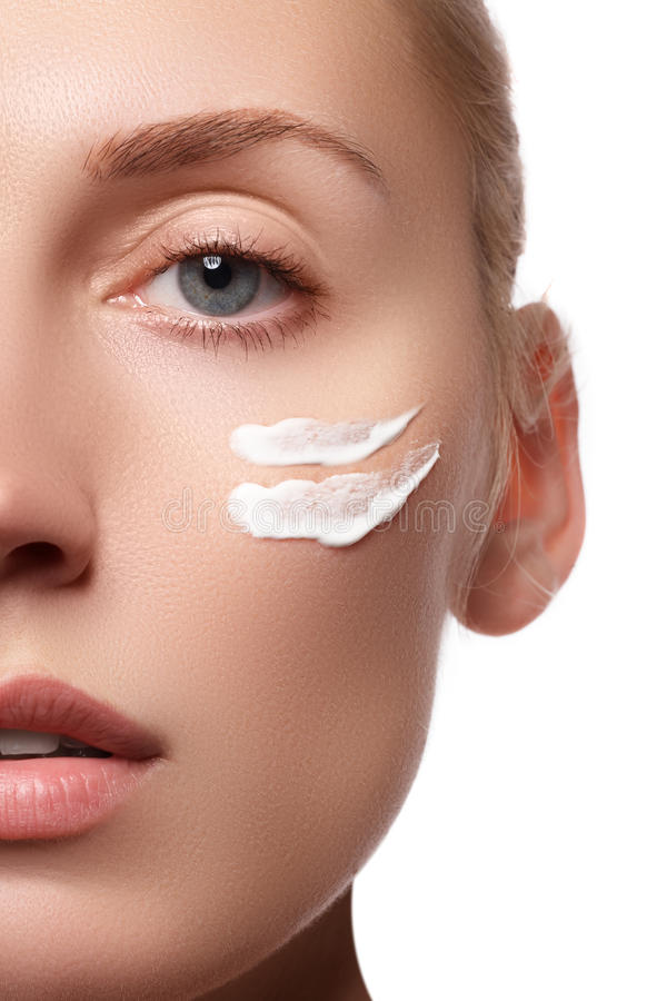 Beautiful face of young woman with cosmetic cream on a cheek. Skin care concept. Closeup portrait isolated on white. Close-up royalty free stock photos