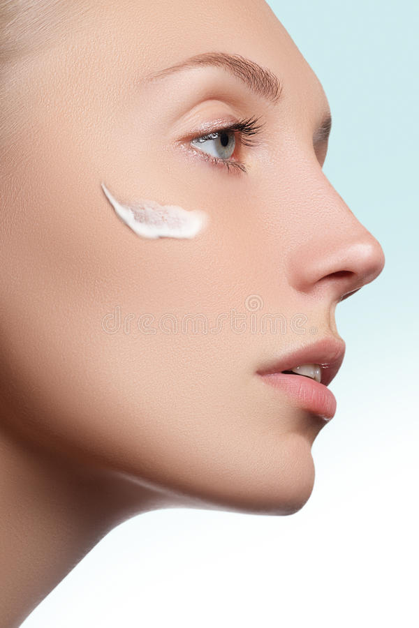 Beautiful face of young woman with cosmetic cream on a cheek. Skin care concept. Closeup portrait on white. Close-up stock image