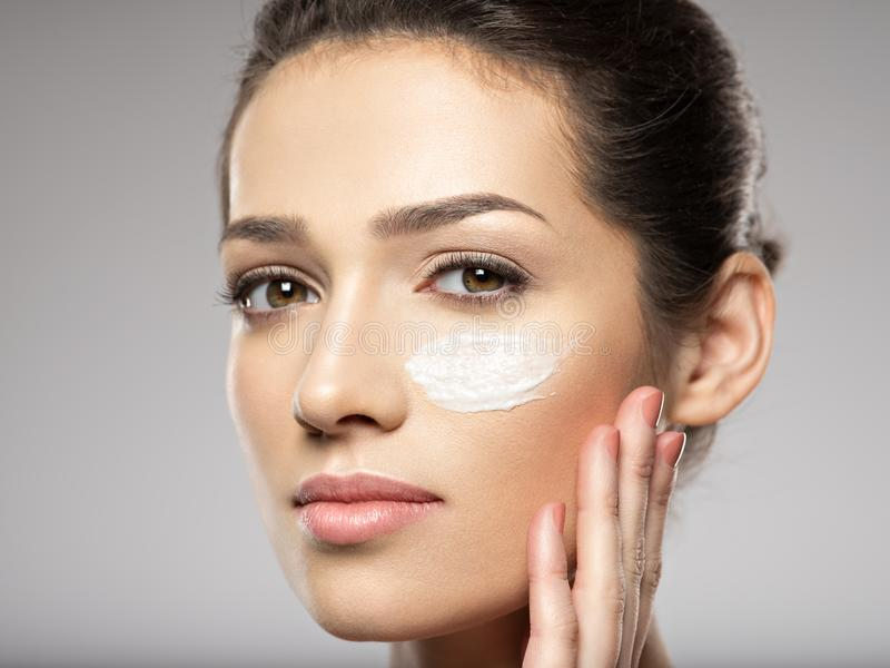 Beautiful face of young woman with cosmetic cream on face stock images