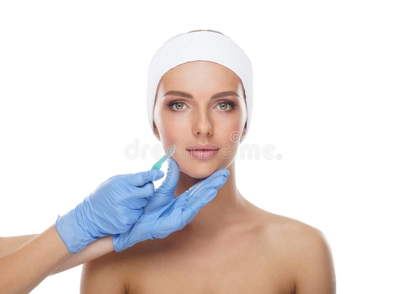 Beautiful face of the young woman and the medical scalpel in doctor`s hands isolated on white. Plastic surgery and face royalty free stock photo