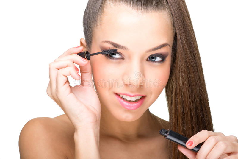 Beautiful fair skinned woman using mascara royalty free stock image