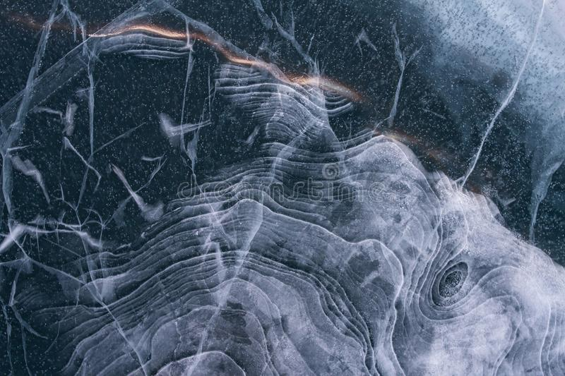 Beautiful fairy-tale texture of the blue ice of Lake Baikal with waves and bubbles. royalty free stock images