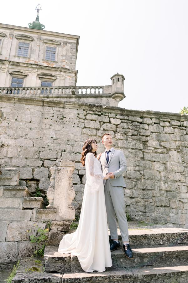 Beautiful fairytale newlywed Asian couple holding hands and kissing near old medieval castle stock images