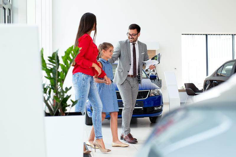 Family buying a new car in the car dealership saloon royalty free stock image