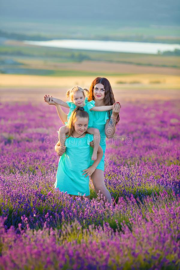 Beautiful family of cute girls enjoy life with girl power on sunset meadow of lavender. Walking mom and daughters in the field of. Lavender stock photo