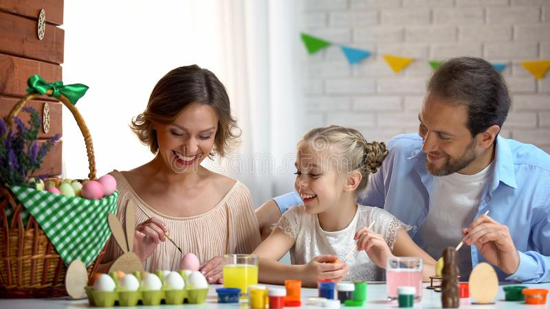 Beautiful family decorating Easter eggs with colorful paint, ancient traditions royalty free stock photos