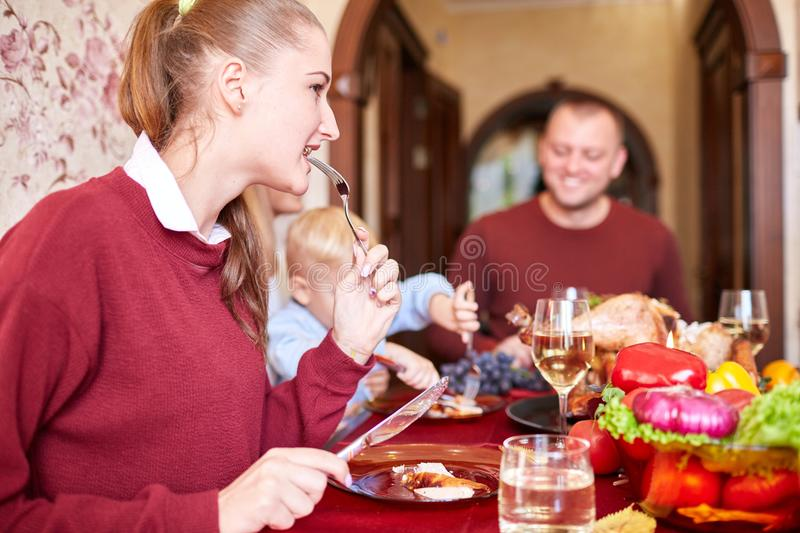 Happy family dining on Christmas on a blurred festive background. Celebrating Thanksgiving concept. Happy new year. royalty free stock photography