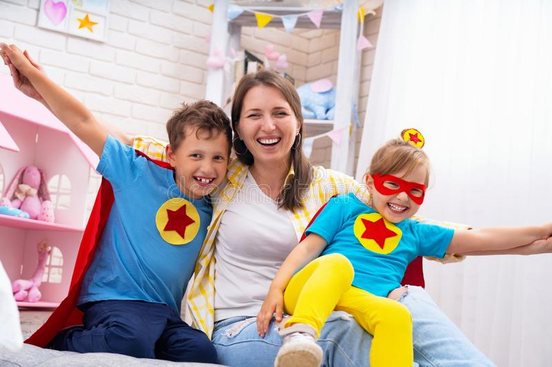 Beautiful family mom and daughter with son dressed in costumes of super heroes in masks and red cloaks fun to play. The concept of royalty free stock photography