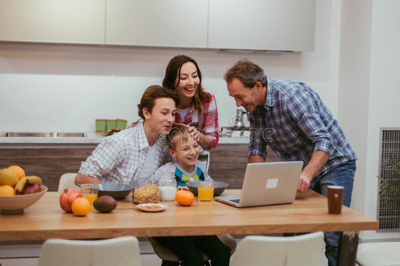 A beautiful family in the morning after a healthy breakfast looking through the laptop and happy smiling all together royalty free stock photos