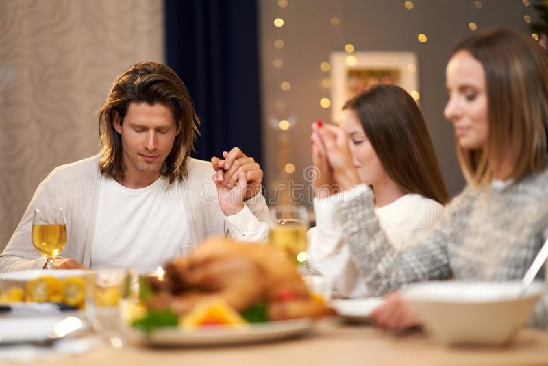 Beautiful family praying over festive dinner at home stock images