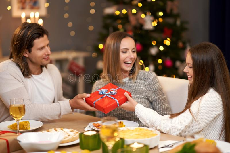 Beautiful family with presents sharing presents during Christmas dinner royalty free stock image