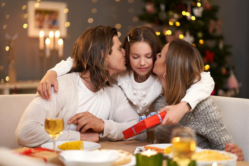 Beautiful family with presents sharing presents during Christmas dinner royalty free stock photo