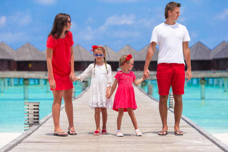 Beautiful family in red having fun on wooden jetty royalty free stock photos