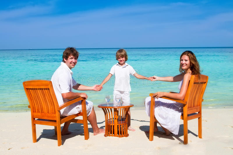 Beautiful family relaxing on beach in wooden chairs stock image