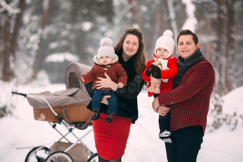 A beautiful family with retro pram walks through the winter snowy forest royalty free stock photo