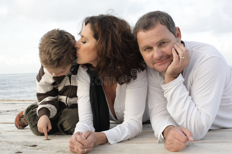 Beautiful family of three on a pier. Young beautiful family of three on a pier royalty free stock image
