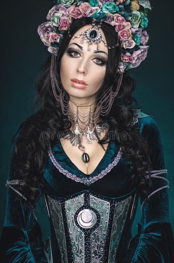 Beautiful fantasy elf woman in floral crown. And medieval dress royalty free stock image